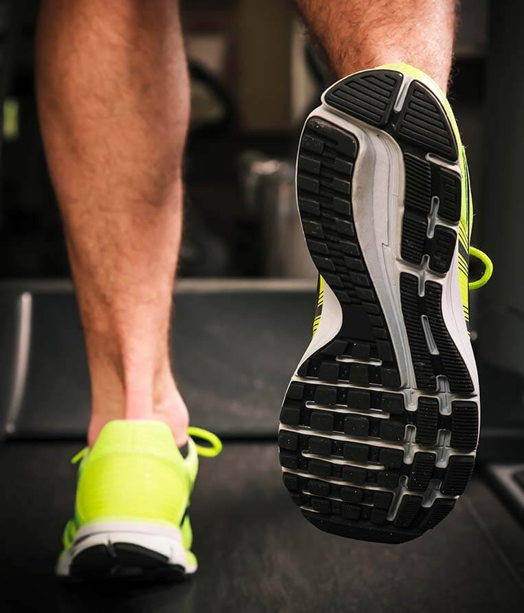 man running on treadmill with podiatrist approved footwear
